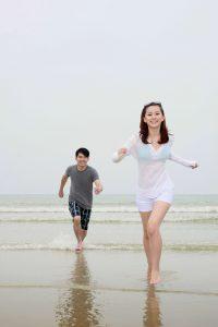 Virgo man chasing a woman through the waves on a beach